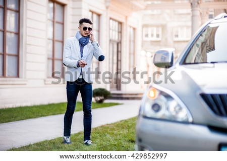 Stylish man goes to his own luxury car disabling protection. Talking on the phone