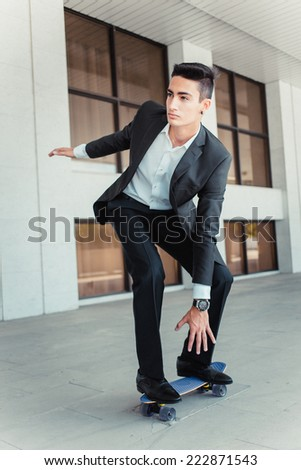 Stylish successful businessman riding a skateboard