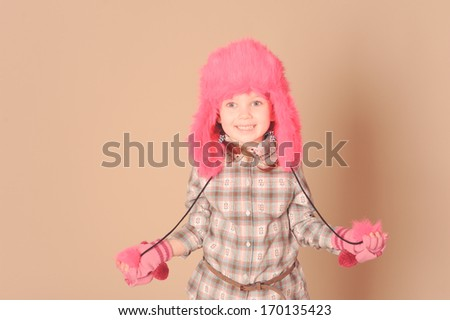 Stylish young baby girl in pink fur winter hat at beige background in studio