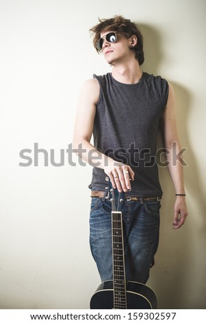 stylish young blonde hipster man playing guitar on white background
