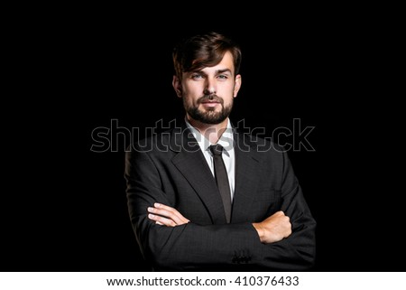 Stylish young businessman on black background. Businessman looking at camera