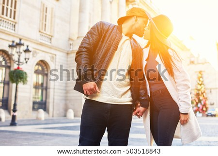 Stylish young couple of hipster kissing on the street during their walk on an autumn morning. Romantic honeymoon in Barcelona for the newlyweds.Love and tenderness of these young people are limitless