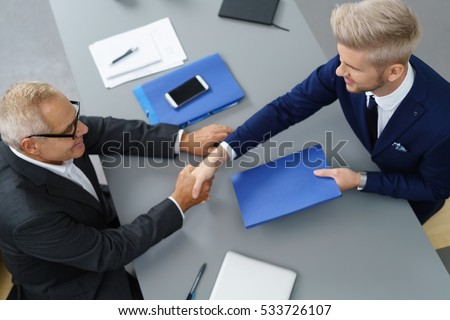 Stylish young job seeker in an employment interview shaking hands with the interviewer and handing over his CV in a blue folder, view from above