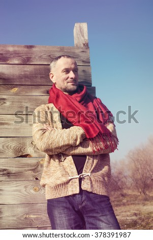 Stylishly dressed bearded man standing on the background of blue sky. Toned image.
