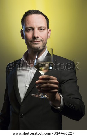 suave man tasting white wine in front of yellow background