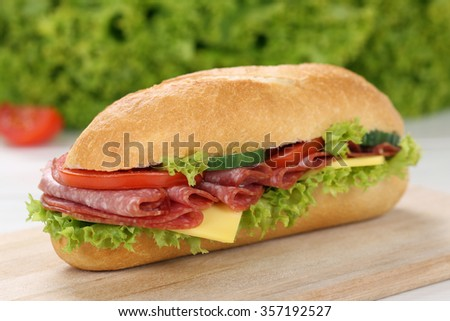 Sub deli sandwich baguette with salami, cheese, tomatoes and lettuce