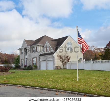 Suburban brick McMansion style home with two car garage white picket fence residential neighborhood blue sky clouds USA