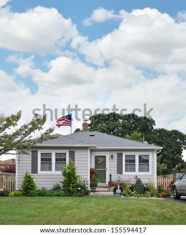 Suburban Bungalow Home American Flag Waving Please do not pick flowers sign residential neighborhood usa blue sky clouds