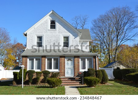 Suburban gable front style home lamppost landscaped in residential neighborhood clear blue sky USA
