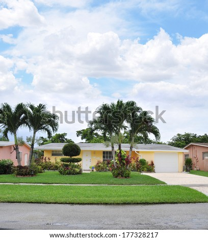 Suburban Ranch beautifully landscaped home in residential neighborhood USA blue sky clouds