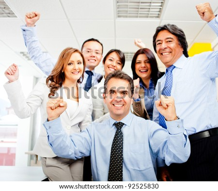 Successful business team celebrating with arms up at the office