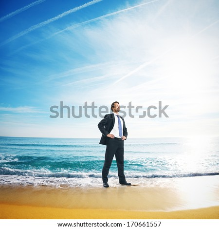 Successful businessman standing on a tropical beach