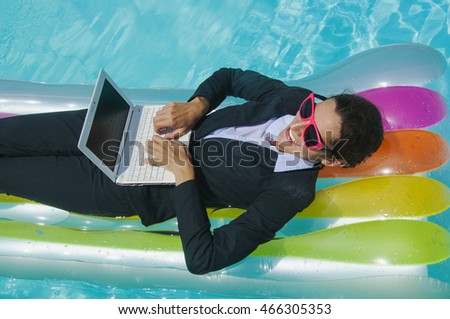 Successful  businesswoman working on floating mattress in swimming pool