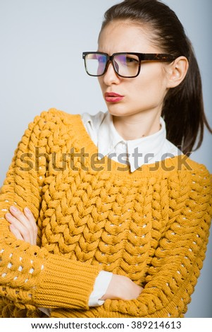 successful girl looks in astonishment, wearing glasses isolated in the studio