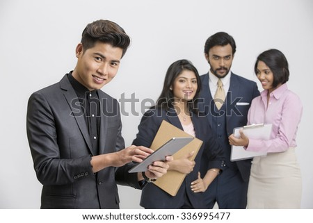 Successful Indian businessman working in tablet with his busy colleagues on white background.