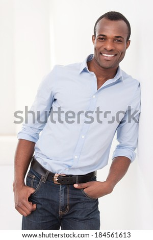 Successful man. Cheerful young black man leaning at the wall and smiling at camera