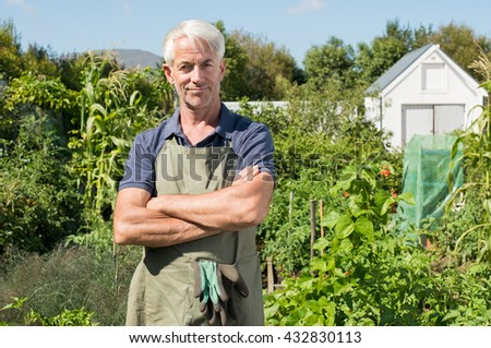 Successful mature man in field. Portrait of a senior man looking at camera in vegetable garden. Happy gardener satisfied and smiling.