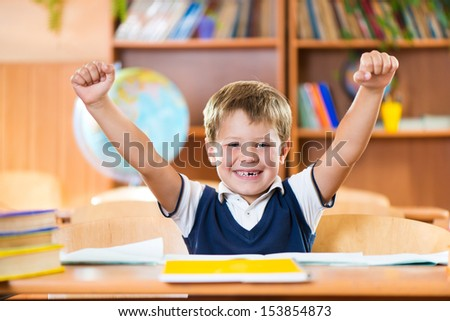 Successful schoolboy with hands up sitting at desk in classroom