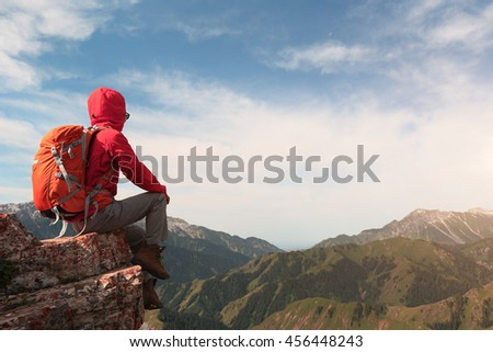 successful woman backpacker enjoy the view on mountain peak cliff