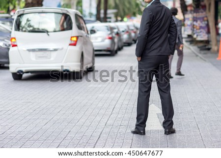 Successful young businessman standing infrontof car.