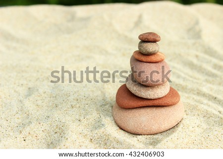 Summer background with stack of pink stones on yellow sea sand. Concept for summer theme