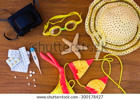Summer beach accessories and medicine on table. Concept of medication required in journey