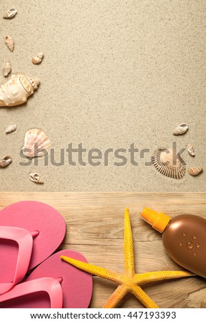 Summer concept with pink flip flops, yellow starfish, suntan oil and shells on sandy beach background. Top view