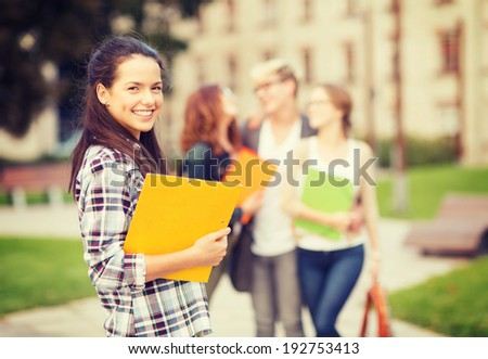 summer holidays, education, campus and teenage concept - smiling teenage girl with folders and classmates on the back