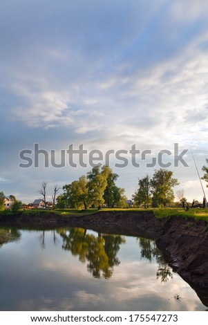 summer landscape oak grove on the shore of a calm river and cloudy sky before sunset