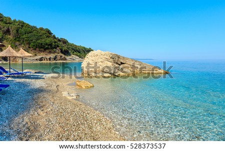 Summer morning Pulebardha beach with sunbeds, strawy sunshades and pebble (Saranda, Albania).
