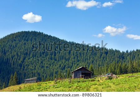 Summer mountain plateau landscape with farm shed on hill top