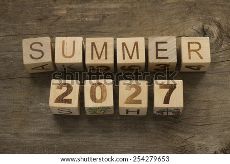 Summer 2027 on wooden blocks on a wooden background
