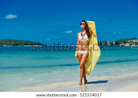 Summer portrait of a beautiful girl in bikini walking on a beach