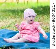 Summer portrait of beautiful baby on the lawn - stock photo