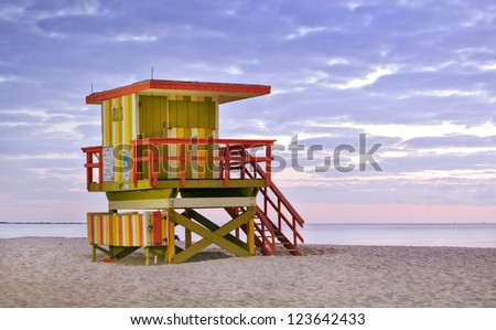 Summer scene in Miami Beach Florida, with a colorful lifeguard house in a typical Art Deco architecture, moments before sunrise with blue sky in the background. Light painting and long exposure.