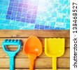 Summer toys on wooden deck over swimming pool - stock photo
