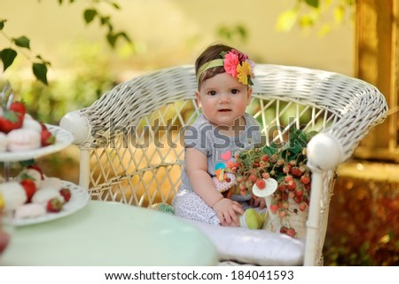 summer vacation at a table in the garden with berries sitting in a wicker chair cute little girl with a flower on her head