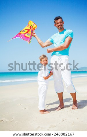 Summer vacation - Cute boy with his mother flying kite beach outdoor