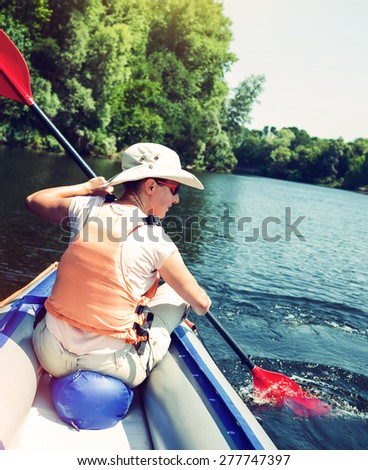 Summer vacation - Young woman kayaking on river. Vintage toning