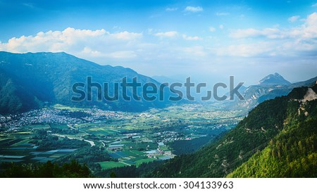 Summer view over an Alpine valley in Northern Italy showing the city of Levico Terme.