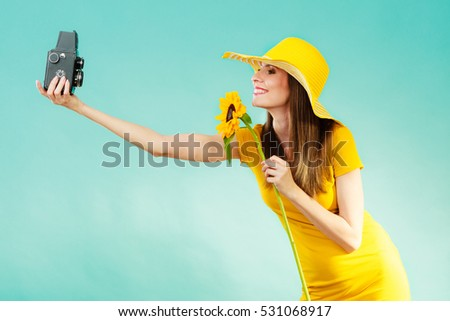 summer woman wearing yellow dress and hat with sunflower taking self picture with old vintage camera on vivid blue background