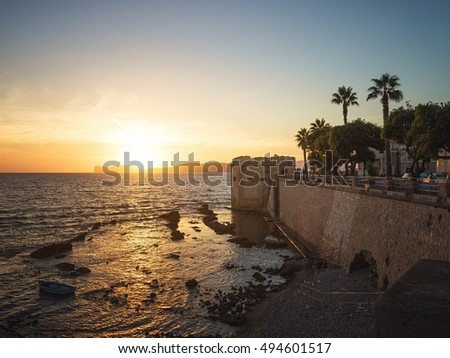Sun Sets over Capo Caccia Cliffs Viewed from the City of Alghero, Sardinia, Italy