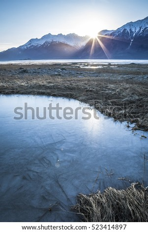 Sun setting behind mountains on the Chilkat river beaches near Haines Alaska with a frozen pond in the foreground.