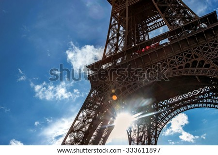Sun shines through construction Eiffel Tower