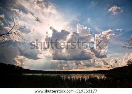 Sunbeams through clouds - scenic cloudscape above still lake