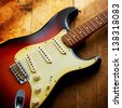 Sunburst color double cutaway electric solid body guitar, on a grungy wooden surface - stock photo