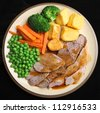 Sunday roast lamb dinner with roast potatoes, broccoli, peas, carrots and gravy. - stock photo
