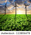 sunflower field with wind turbines in the sunset - stock photo