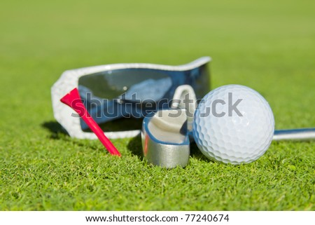 sunglasses on green with putter and golf ball (golf leisure concept)
