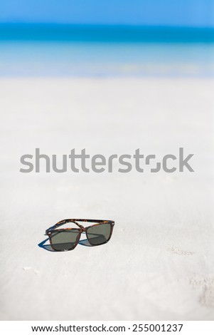 Sunglasses on the beach for summer concept
